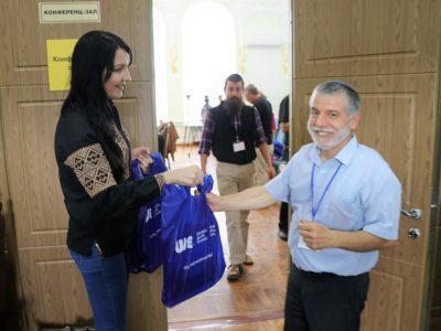 Адміністратор UJE в Україні Світлана Шиман вручає учасникам Конференції пакети з подарунками – останніми книжками, виданими за сприяння Фундації.