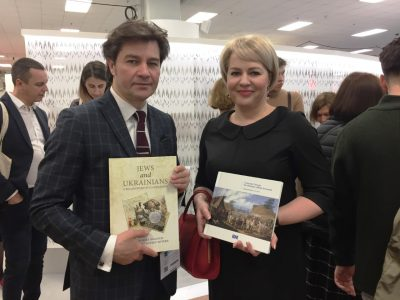"Ukraine's Minister of Culture Yevhen Nyshchuk (left) and Natalia Galibarenko, Ambassador Extraordinary and Plenipotentiary of Ukraine to the United Kingdom of Great Britain and Northern Ireland (right) hold two books sponsored by the Ukrainian Jewish Encounter at the London Book Fair. The books are ""Jews and Ukrainians: A Millennium of Co-Existence"" by UJE board member Paul Robert Magocsi and Yohanan Petrovsky-Shtern, and ""A Journey Through the Ukrainian Jewish Encounter: From Antiquity to 1914"" by UJE co-director Alti Rodal."