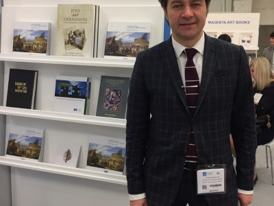 Ukraine's Minister of Culture Yevhen Nyshchuk stands by the Ukrainian Jewish Encounter's display at the London Book Fair. UJE was a sponsor of the Ukraine country booth.