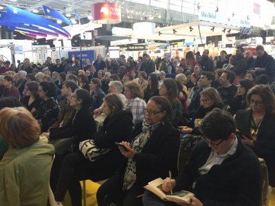 Аудиторія під час панельної дискусії Паризького «Salon du Livre»/Паризької книжкової ярмарки. Учасниками були: Андрій Курков, відомий український письменник, який також є президентом громадської організації «PEN Ukraine» (ліворуч); Ірена Карпа, популярна письменниця та співачка (по центру); та Ірина Славінська, одна з ведучих програми «Зустрічі» каналу «Громадське радіо», що виходить за підтримки UJE (праворуч).