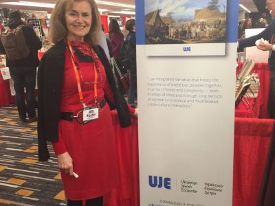 "UJE Co-Director Alti Rodal stands before a banner promoting her book ""A Journey Through the Ukrainian-Jewish Encounter: From Antiquity to 1914."""