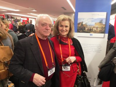 "UJE board member Berel Rodal and UJE Co-Director Alti Rodal stand before a banner promoting the book ""A Journey Through the Ukrainian-Jewish Encounter: From Antiquity to 1914."""