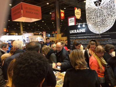 Андрій Курков, добре знаний у Франції український письменник підписує книги біля Українського стенду на Міжнародному Паризькому книжковому салоні.