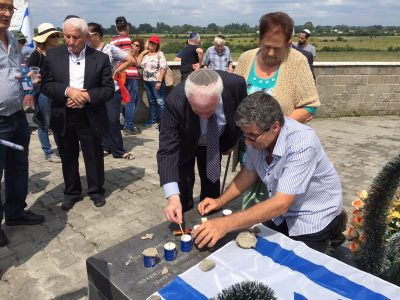 UJE Board Member Berel Rodal lights one of the six candles traditionally lit at Holocaust memorials. Six candles represent the six million Jews who were murdered during the Holocaust.