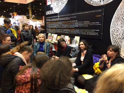 Ірина Дмитришин, перекладач (праворуч), Мар'яна Савка, видавництво «Старого лева» (по центру) та Ірина Славінська, модератор (ліворуч) біля Українського стенду на Міжнародному Паризькому книжковому салоні.